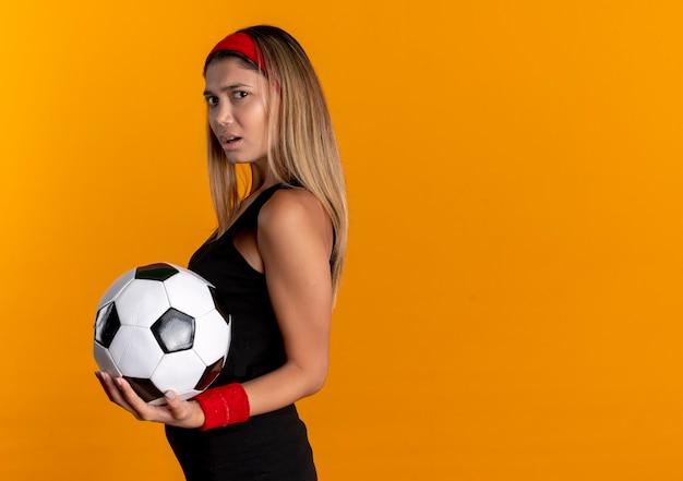 Junges fitnessmädchen in der schwarzen sportbekleidung und im roten stirnband, die fußball halten, missfiel das stehen über orange wand