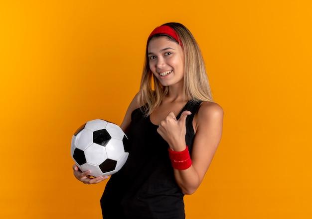 Junges fitnessmädchen in der schwarzen sportbekleidung und im roten stirnband, die fußball lächelnd zeigen, zeigt daumen hoch stehend über orange wand