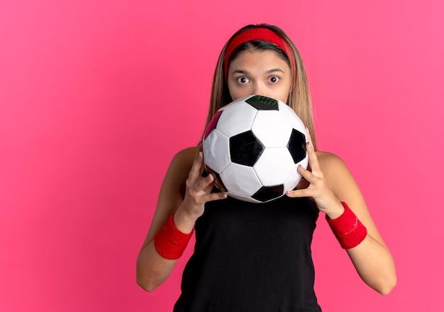 Junges fitnessmädchen in der schwarzen sportbekleidung und im roten stirnband, die fußball suchen, der überrascht ihr gesicht versteckt über rosa wand hält