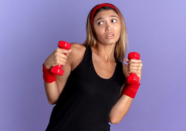 Junges fitnessmädchen in der schwarzen sportbekleidung und im roten stirnband, die mit den hanteln arbeiten, die verwirrt über der blauen wand stehen