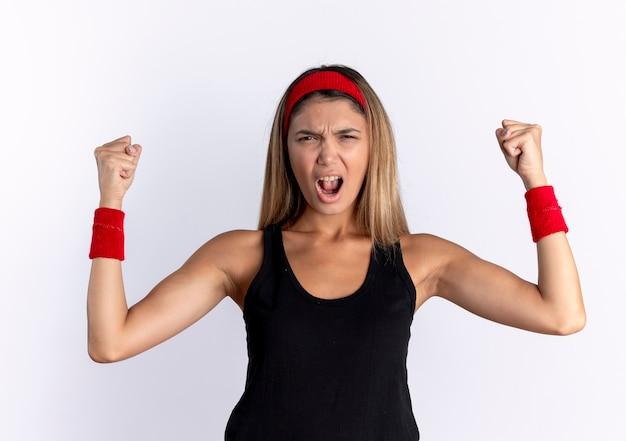 Junges fitnessmädchen in der schwarzen sportbekleidung und im roten stirnband, die wild geballt werden und die fäuste erheben, die mit wütendem gesicht schreien, das über weißer wand steht