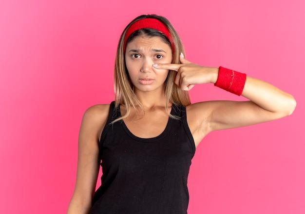 Junges fitnessmädchen in der schwarzen sportbekleidung und im roten stirnband zeigen mit dem finger an ihrer nase mit dem traurigen ausdruck, der über rosa wand steht