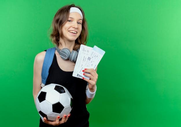 Junges fitnessmädchen in schwarzer sportbekleidung mit rucksack und stirnband, die fußball- und flugtickets lächelnd fröhlich über grüner wand stehend halten