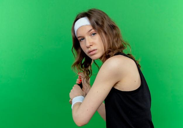 Junges fitnessmädchen in schwarzer sportbekleidung mit schwingendem baseballschläger des stirnbandes mit ernstem gesicht, das über grüner wand steht