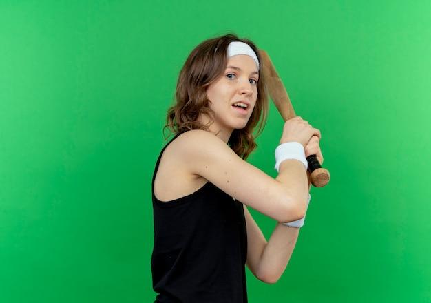 Junges fitnessmädchen in schwarzer sportbekleidung mit stirnband, das baseballschläger hält, verwirrt über grüner wand stehend
