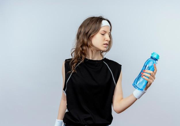 Junges fitnessmädchen in schwarzer sportbekleidung mit stirnband, das flasche wasser hält, das es mit ernstem gesicht betrachtet, das über weißer wand steht
