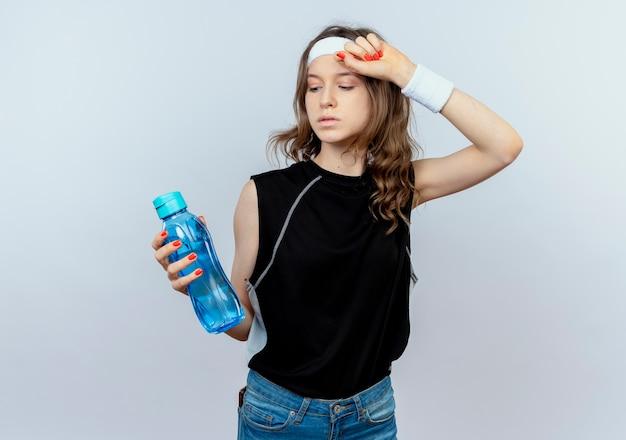 Junges fitnessmädchen in schwarzer sportbekleidung mit stirnband, das flasche wasser hält, das müde steht über weißer wand steht