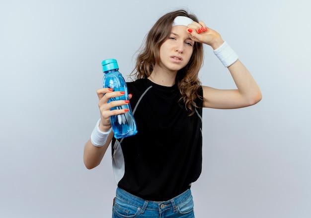 Junges fitnessmädchen in schwarzer sportbekleidung mit stirnband, das flasche wasser hält, das müde und erschöpft über weißer wand steht