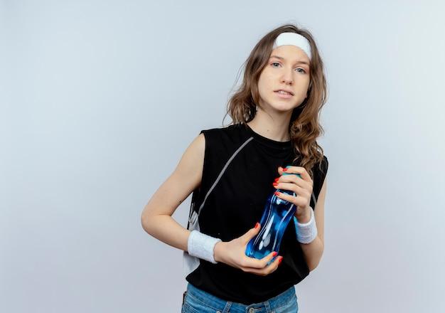Junges fitnessmädchen in schwarzer sportbekleidung mit stirnband, das flasche wasser verwirrt steht über weißer wand