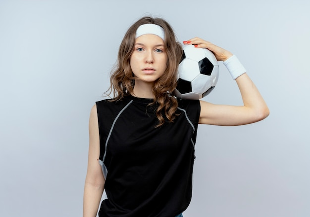 Junges fitnessmädchen in schwarzer sportbekleidung mit stirnband, das fußball mit ernstem gesicht hält, das über weißer wand steht