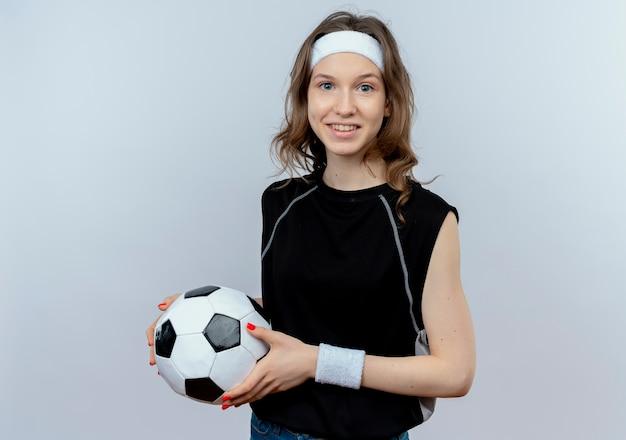 Junges fitnessmädchen in schwarzer sportbekleidung mit stirnband, das fußball mit lächeln auf gesicht steht, das über weißer wand steht