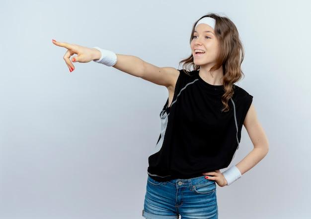 Junges fitnessmädchen in schwarzer sportbekleidung mit stirnband, das lächelnd beiseite schaut und mit dem finger auf etwas steht, das über weißer wand steht
