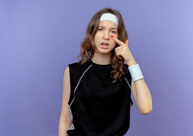 Junges fitnessmädchen in schwarzer sportbekleidung mit stirnband, das mit dem finger auf ihr auge zeigt, das über blauer wand steht