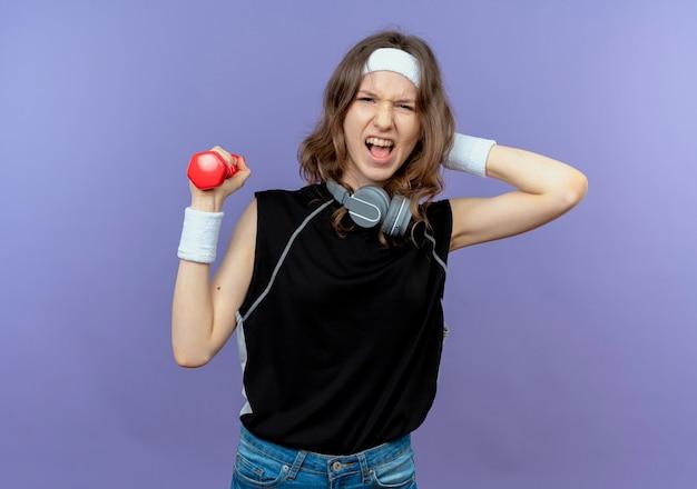 Junges fitnessmädchen in schwarzer sportbekleidung mit stirnband, das mit hantel arbeitet, die über blau verwirrt schaut