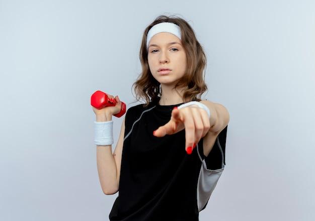 Junges fitnessmädchen in schwarzer sportbekleidung mit stirnband, das mit hantel mit ernstem gesicht ausarbeitet, das mit finger zeigt, der über weißer wand steht