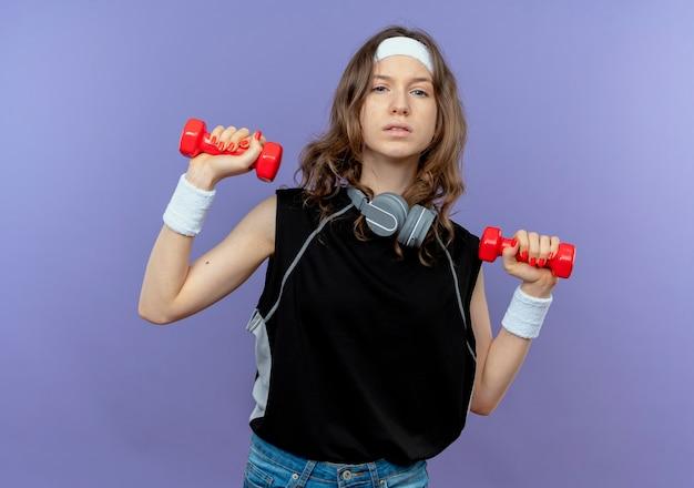 Junges fitnessmädchen in schwarzer sportbekleidung mit stirnband, das mit hanteln arbeitet, die über blau zuversichtlich schauen