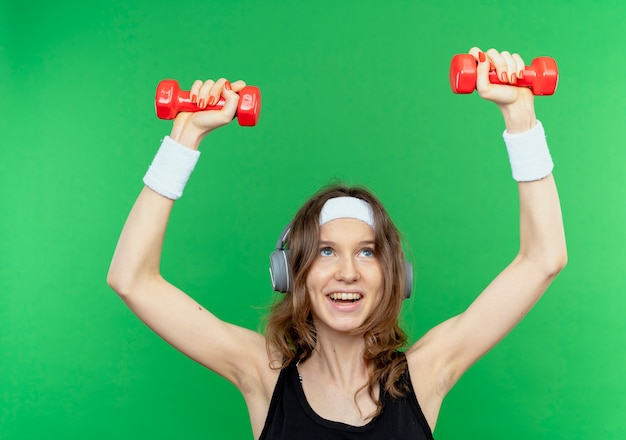 Junges fitnessmädchen in schwarzer sportbekleidung mit stirnband, das mit hanteln herausarbeitet, die fröhlich über grüner wand stehen