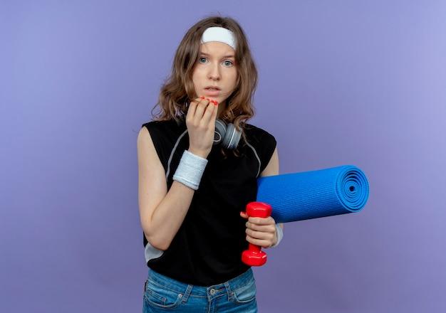 Junges fitnessmädchen in schwarzer sportbekleidung mit stirnband, das yogamatte und hantel hält besorgt und verwirrt über blau