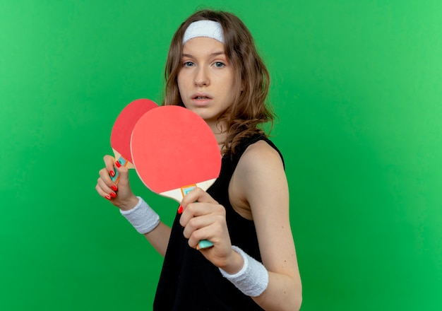Junges fitnessmädchen in schwarzer sportbekleidung mit stirnband, das zwei schläger für tischtennis mit ernstem gesicht hält über grüner wand hält