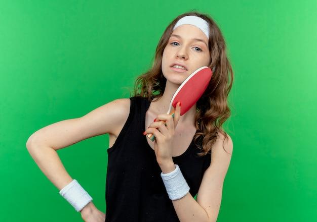 Junges fitnessmädchen in schwarzer sportbekleidung mit stirnband, das zwei schläger für tischtennis mit lächeln auf gesicht über grün hält