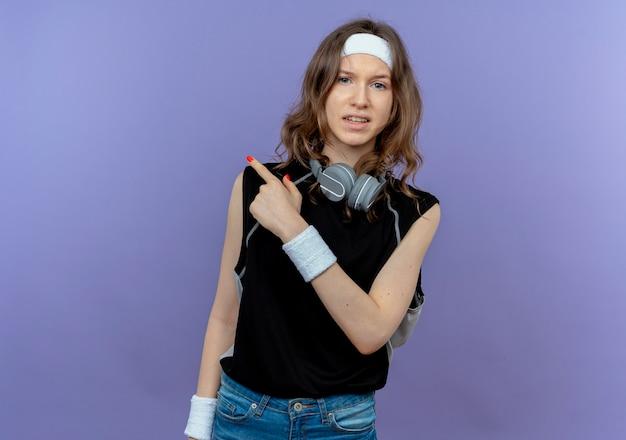 Junges fitnessmädchen in schwarzer sportbekleidung mit stirnband mit skeptischem ausdruck, der zurück zeigt, der über blaue wand steht