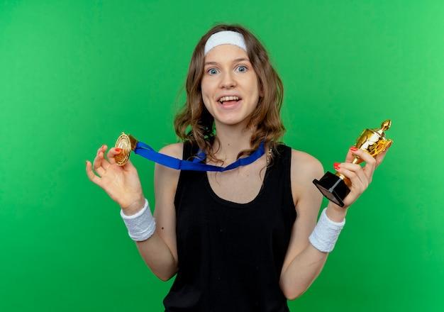 Junges fitnessmädchen in schwarzer sportbekleidung mit stirnband und goldmedaille um den hals, die trophäe glücklich und aufgeregt über grün hält