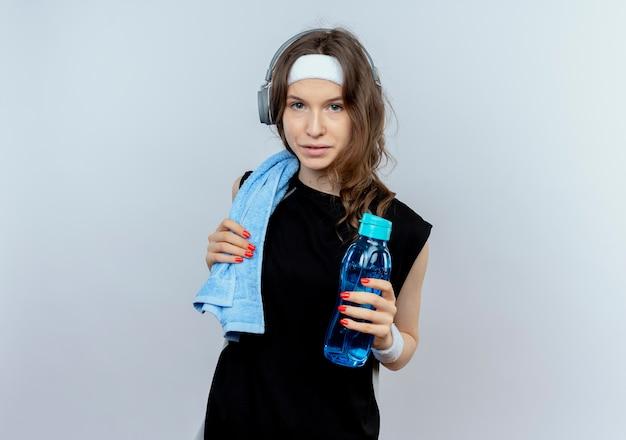 Junges fitnessmädchen in schwarzer sportbekleidung mit stirnband und kopfhörern und handtuch auf schulter, die flasche wasser hält, das sicher steht, über weißer wand steht