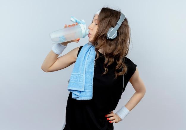 Junges fitnessmädchen in schwarzer sportbekleidung mit stirnband und kopfhörern und handtuch auf schultertrinkwasser nach dem training, das über weißer wand steht