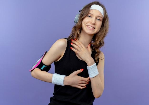 Junges fitnessmädchen in schwarzer sportbekleidung mit stirnband und smartphone-armbinde, die über blauer wand stehen