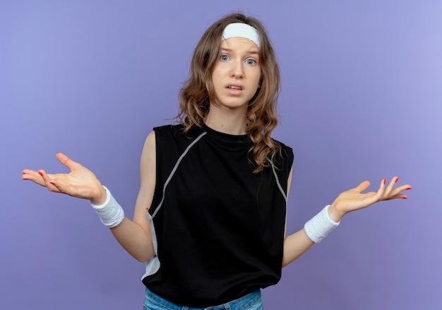 Junges fitnessmädchen in schwarzer sportbekleidung mit verwirrtem stirnband, das arme zu den seiten über blau ausbreitet