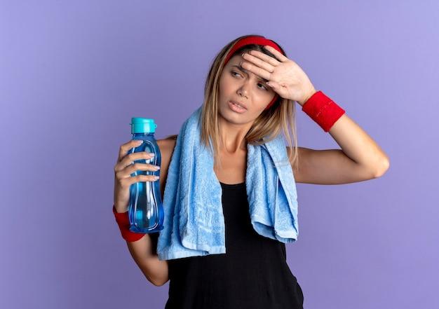 Junges fitnessmädchen in schwarzer sportbekleidung und rotem stirnband mit handtuch um den hals, das flasche wasser hält, das müde und erschöpft nach dem training steht, das über blaue wand steht