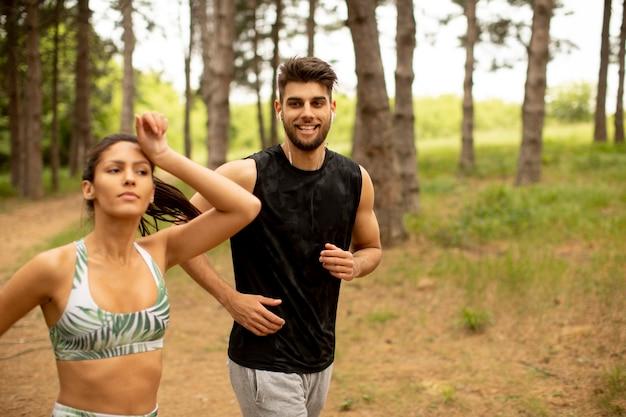 Junges fitnesspaar, das an der waldspur an einem sommertag läuft