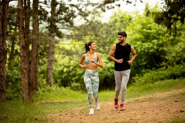 Junges fitnesspaar, das an einem sommertag auf dem waldweg läuft