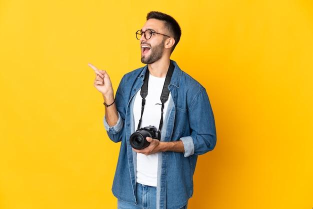 Junges fotografmädchen lokalisiert auf gelbem hintergrund, das beabsichtigt, die lösung beim anheben eines fingers zu realisieren