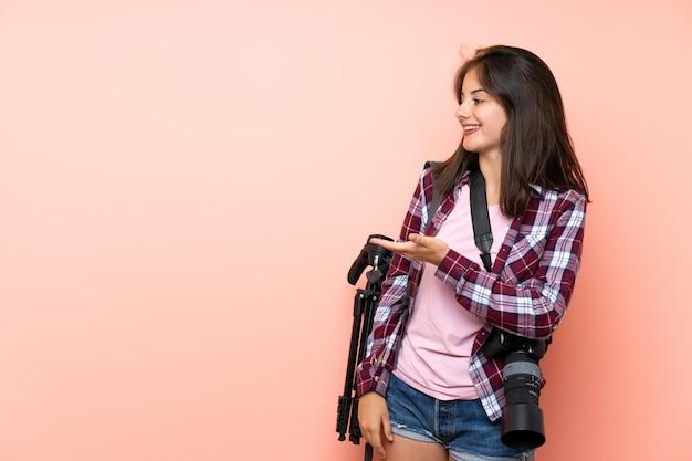 Junges fotografmädchen über ausdehnungshänden der lokalisierten rosa wand zur seite für die einladung zu kommen