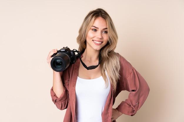 Junges fotografmädchen über der isolierten wand, die mit armen an der hüfte aufwirft und lächelt