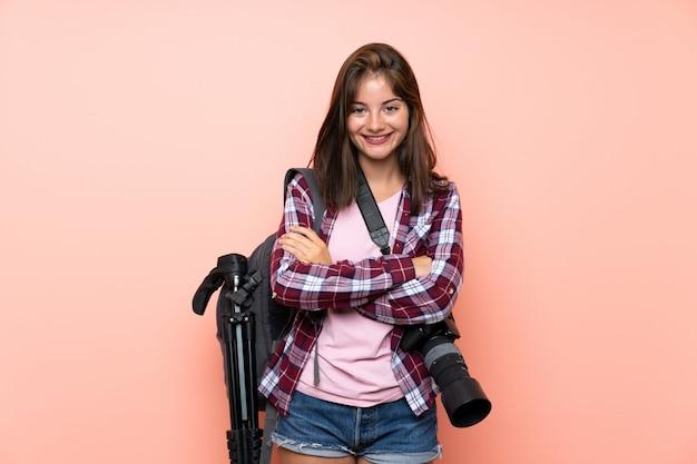 Junges fotografmädchen über getrenntem rosafarbenem wandlachen