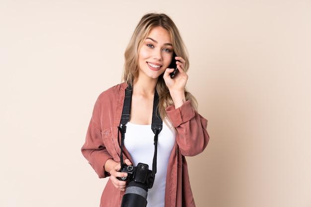 Junges fotografmädchen über isolierter wand, die ein gespräch mit dem handy mit jemandem hält