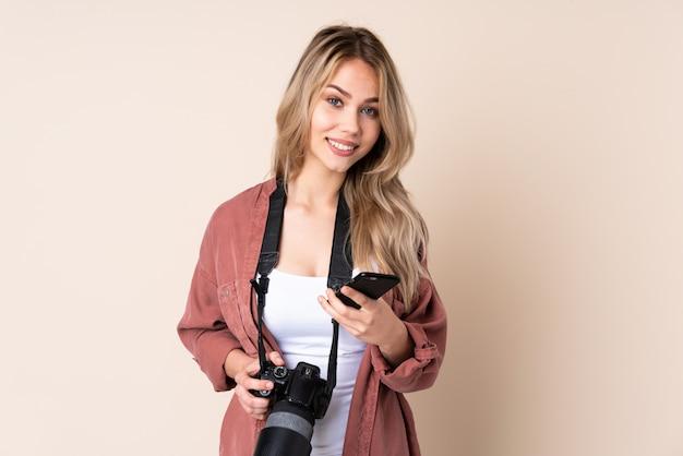 Junges fotografmädchen über isolierter wand, die eine nachricht mit dem handy sendet