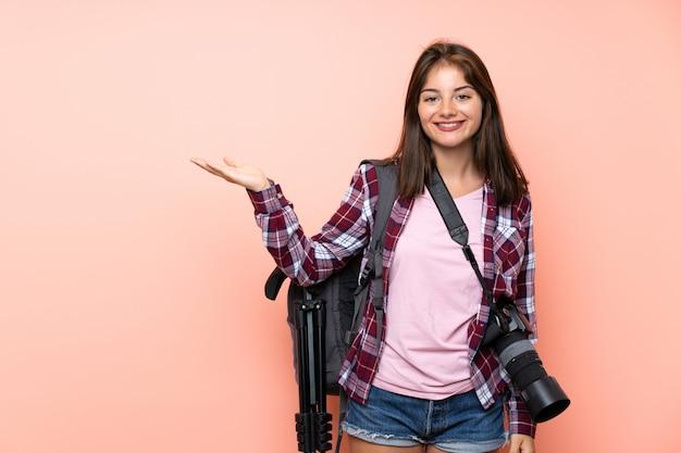 Junges fotografmädchen über lokalisierter rosa wand, die copyspace eingebildet auf der palme hält
