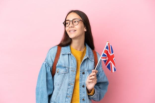 Junges französisches mädchen, das eine britische flagge lokalisiert auf rosa hintergrund hält, der eine idee beim nachschlagen denkt
