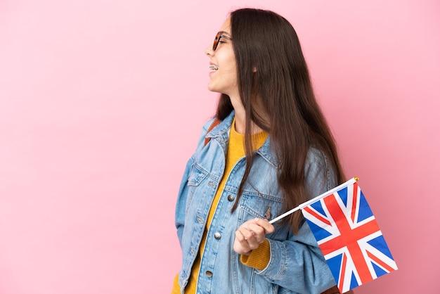 Junges französisches mädchen, das eine britische flagge lokalisiert auf rosa hintergrund hält, der in seitlicher position lacht