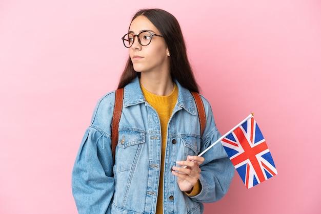 Junges französisches mädchen, das eine britische flagge lokalisiert auf rosa hintergrund hält, der zur seite schaut