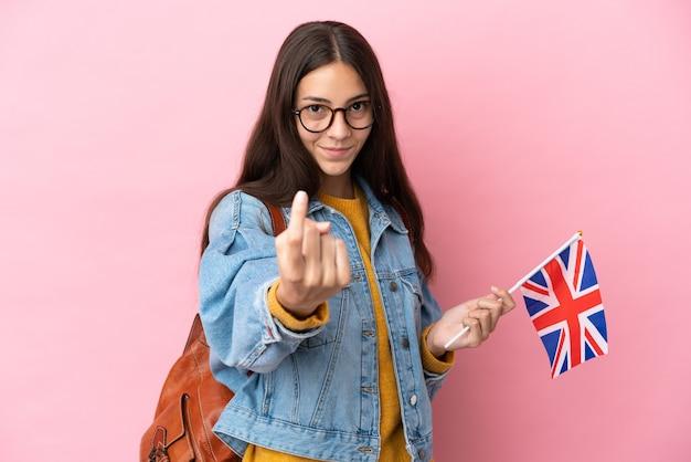 Junges französisches mädchen, das eine britische flagge lokalisiert auf rosa hintergrund hält kommende geste hält