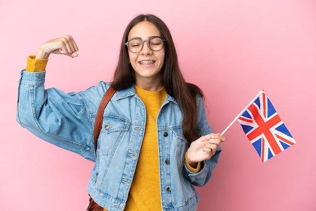 Junges französisches mädchen, das eine britische flagge lokalisiert auf rosa hintergrund hält starke geste hält