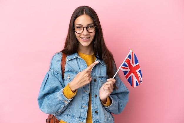 Junges französisches mädchen, das eine flagge des vereinigten königreichs hält, die auf rosa hintergrund isoliert ist und auf die seite zeigt, um ein produkt zu präsentieren?