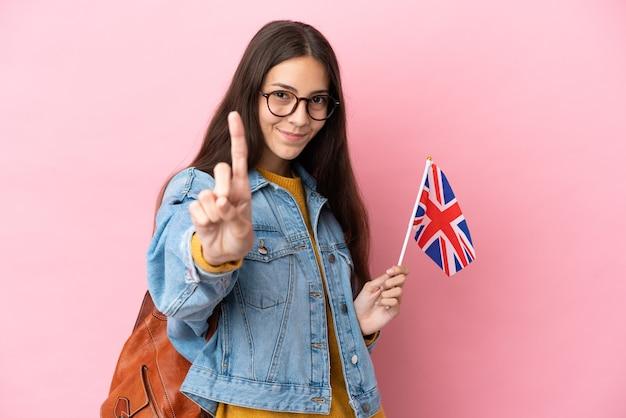 Junges französisches mädchen, das eine flagge des vereinigten königreichs hält, die auf rosa hintergrund isoliert ist und einen finger zeigt und hebt