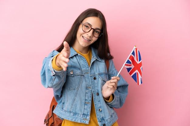 Junges französisches mädchen, das eine flagge des vereinigten königreichs hält, die auf rosafarbenem hintergrund isoliert ist und sich die hände schüttelt, um ein gutes geschäft abzuschließen