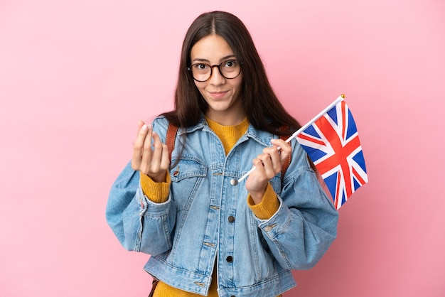 Junges französisches mädchen, das eine flagge des vereinigten königreichs isoliert auf rosa hintergrund hält und geldgeste macht