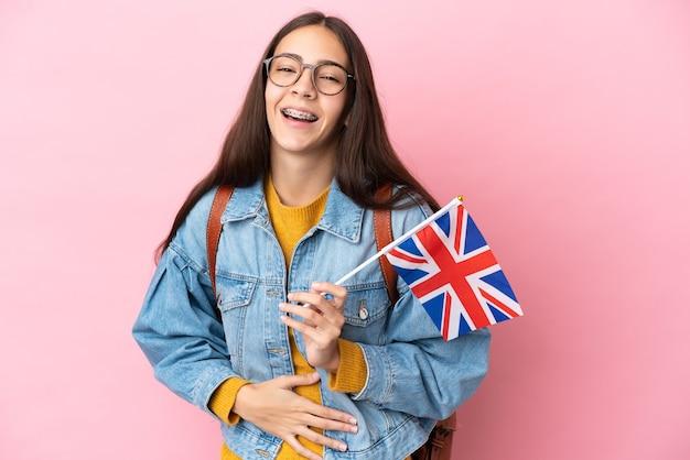 Junges französisches mädchen, das eine flagge des vereinigten königreichs isoliert auf rosa hintergrund hält und viel lächelt